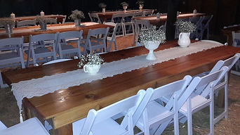 Handmade wooden tables with white folding chairs set up inside the barn.