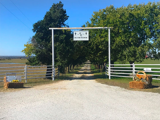 Entrance to the Double K Rustic Ranch wedding barn venue down the tree lined driveway.