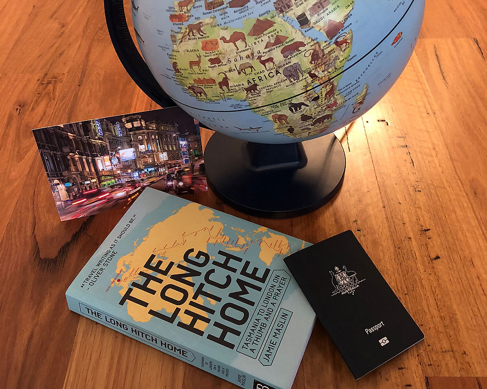 The Long Hitch Home book, globe, postcard and passport
