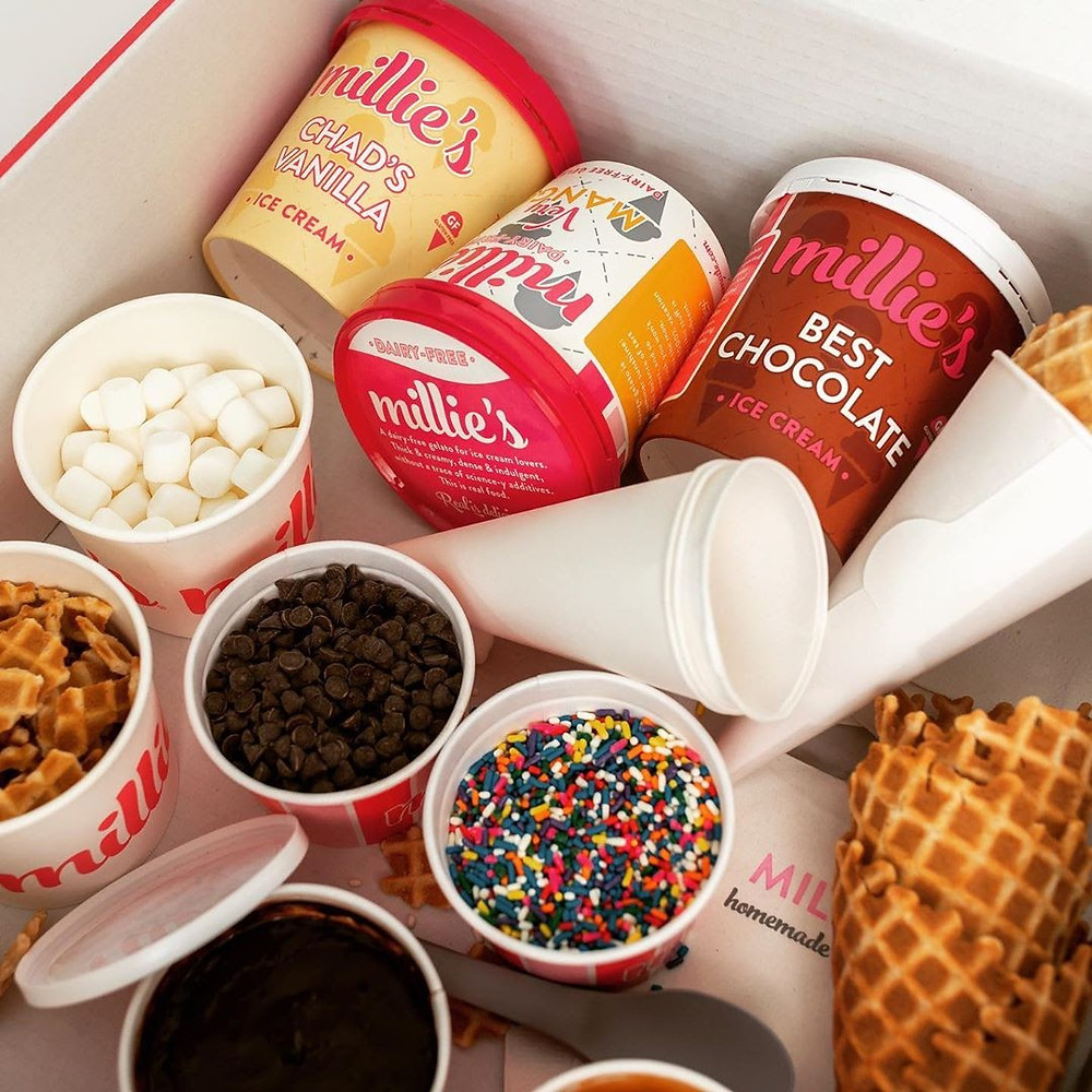 A box with an assortment of ice cream, toppings, and cones from Millie's Homemade Ice Cream