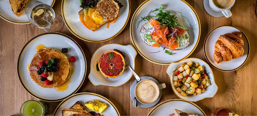 Overhead shot of brunch items at The Speckled Egg in Pittsburgh: pancakes, bagel & lox, hash, dippy eggs, coffee, grapefruit