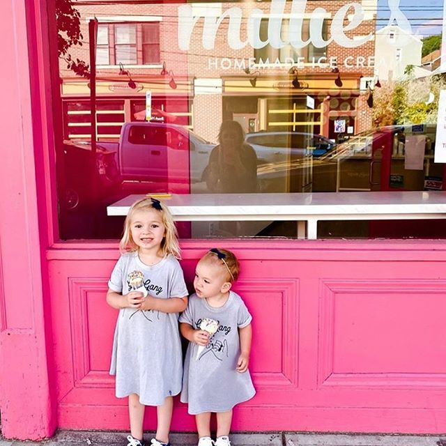 Two small girls hold ice cream cones in front of Millie's Homemade Ice Cream