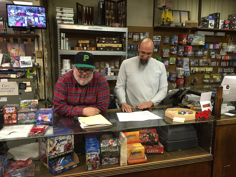 The owners of Games Unlimited grin as they stand behind the counter