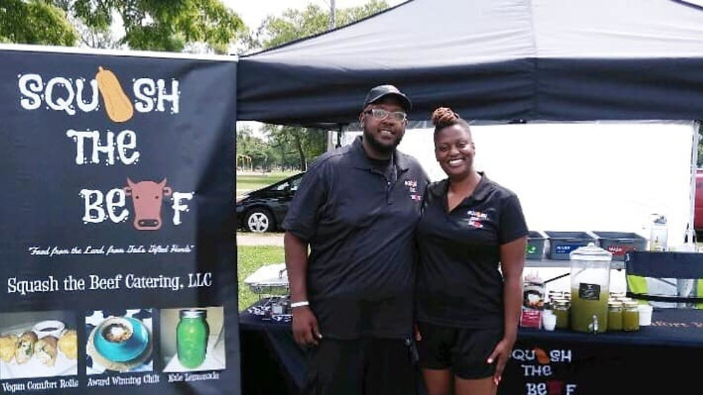 Candace and Kurtis of Squash the Beef stand in front of their festival set up