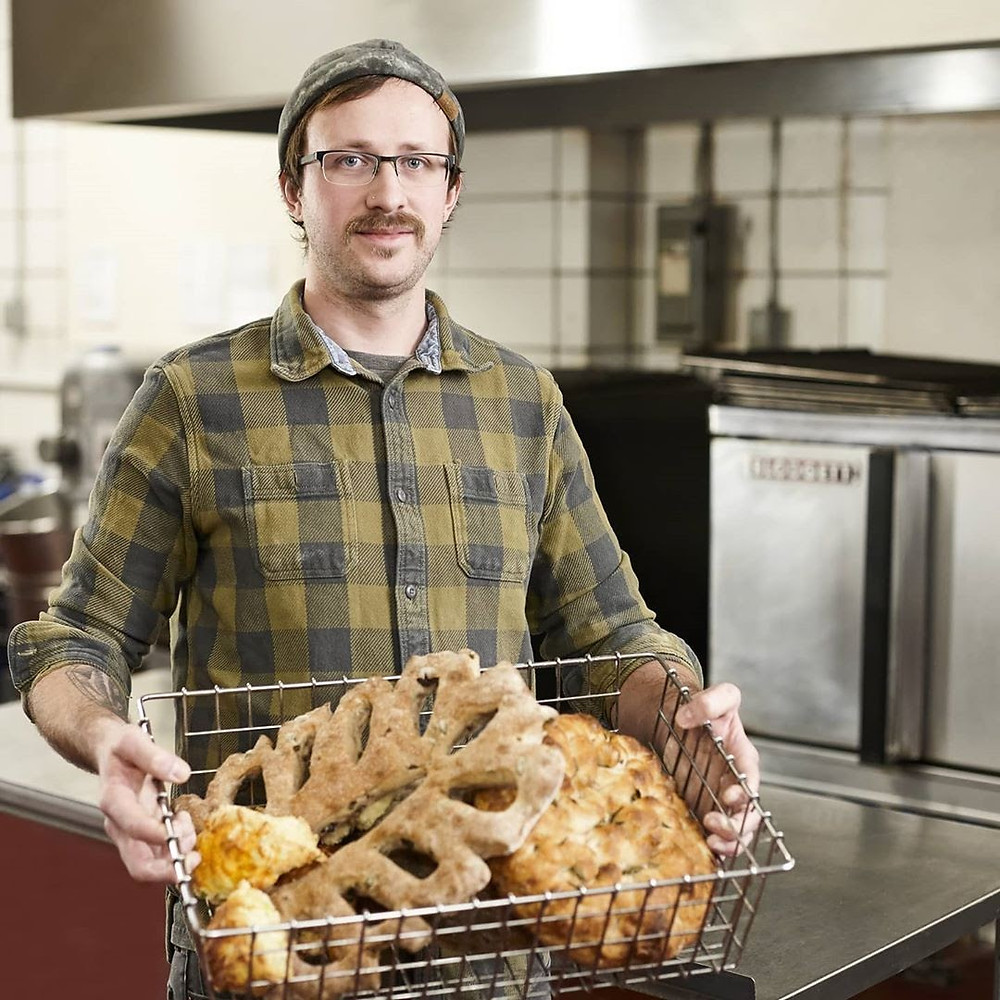 Ian Herrington, owner of Leavened Bakery in Cleveland, holds up a basket of bread