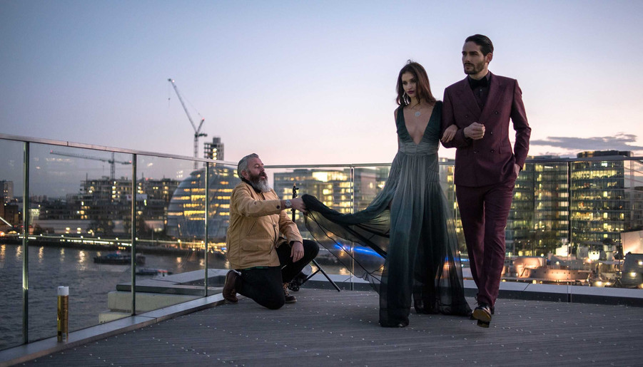 female and male models on a large terrace of a luxury apartment in London Bridge, art director and fashion stylist Layra Harmony working with a photographer on set behind the scenes, UK