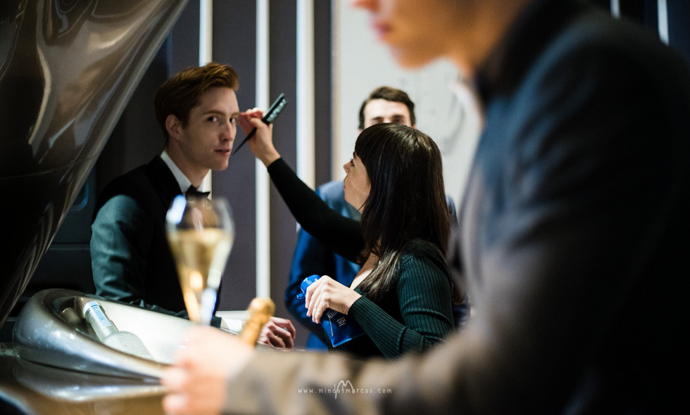 Make up artist working with a male model behind the scenes of a photo shoot production for a high end brand advertorial advertising campaign, Home House, London, UK