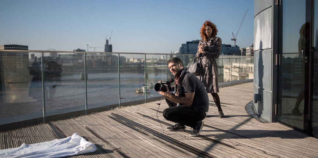 On a large terrace of a luxury apartment in London Bridge, art director and fashion stylist Layra Harmony working with a photographer on set behind the scenes, UK