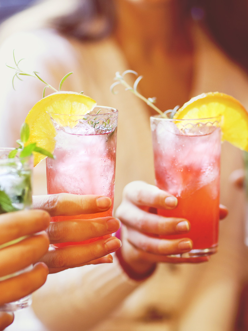 Young men and women drinking cocktail at