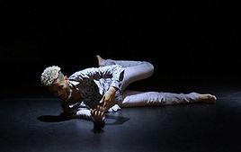 René Loui, com calça e camisa cinza, faz movimentação no chão do palco preto.