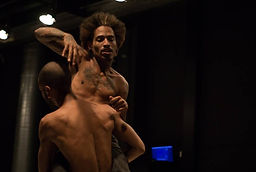 René e Diogo, dois homens negros sem camisa em um teatro.René carrega Diogo no colo.