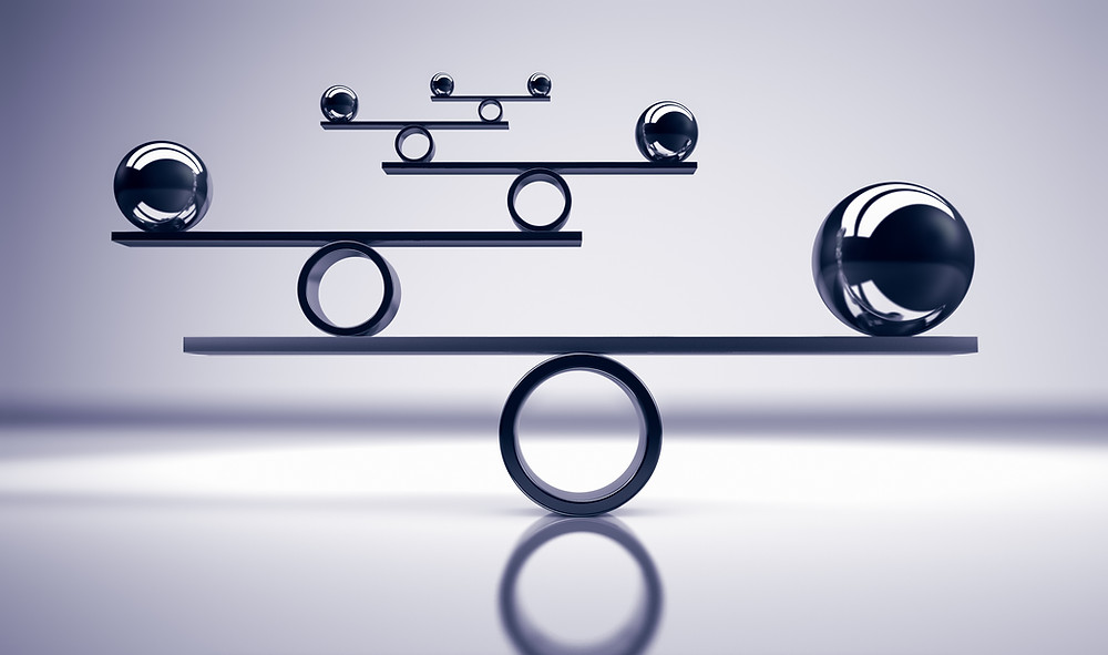 Metal spheres balancing on flat metal strip balancing on a cylinder.