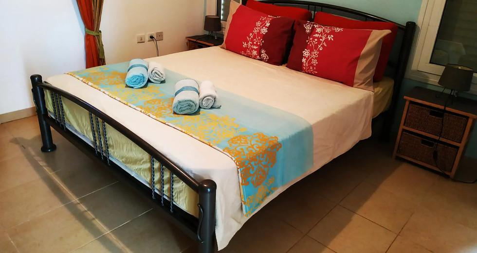 קיץ.חדר שינה זוגי וממוזג בקומת הכניסה עם חדר רחצה מובנה.קוים פשוטים ונקיים. Summer. A double airconditioned double bedroom with an onsuite shower room