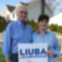 A Sayville couple posing wit Liuba sign in front of their home.