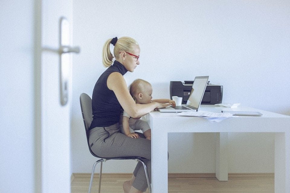 Young mother sitting at a desk with a young child in her lab.