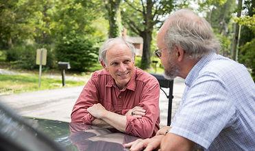 Sam Edney talks with a neighbor leaning on the hood of the car.