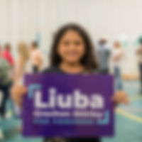 Photo of a young girl holding a sign in support of Liuba Grechen Shirley