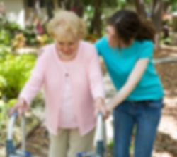 Caregiver helping kind lady with walker
