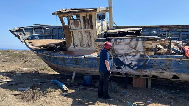 Un'imbarcazione abbandonata a Lampedusa  con un murales di Morden Gore