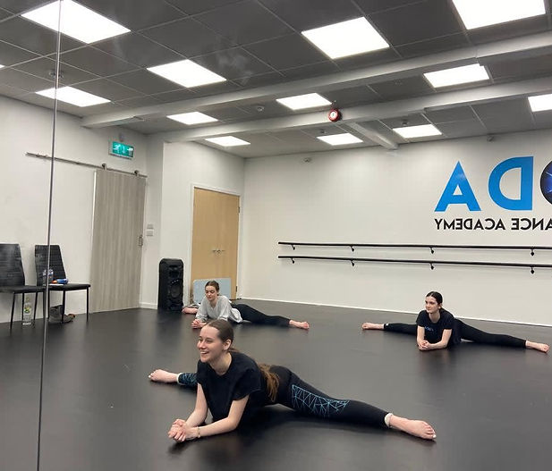 dancers performing splits in studio