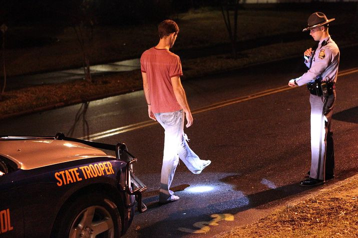 A Georgia State Patrol Trooper conducts standardized field sobriety tests (FSTs) on a suspected drunk driver on a public road at night.