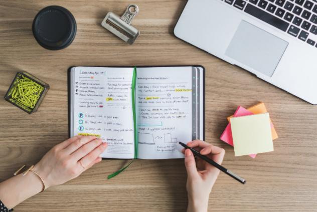 びっしりと書かれたノートに何か書こうとしている人の手