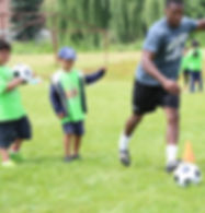 camp kids playing soccer with coach