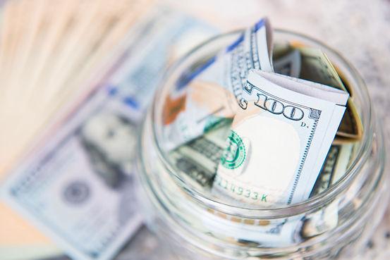 A jar filled with hundred doallr bills