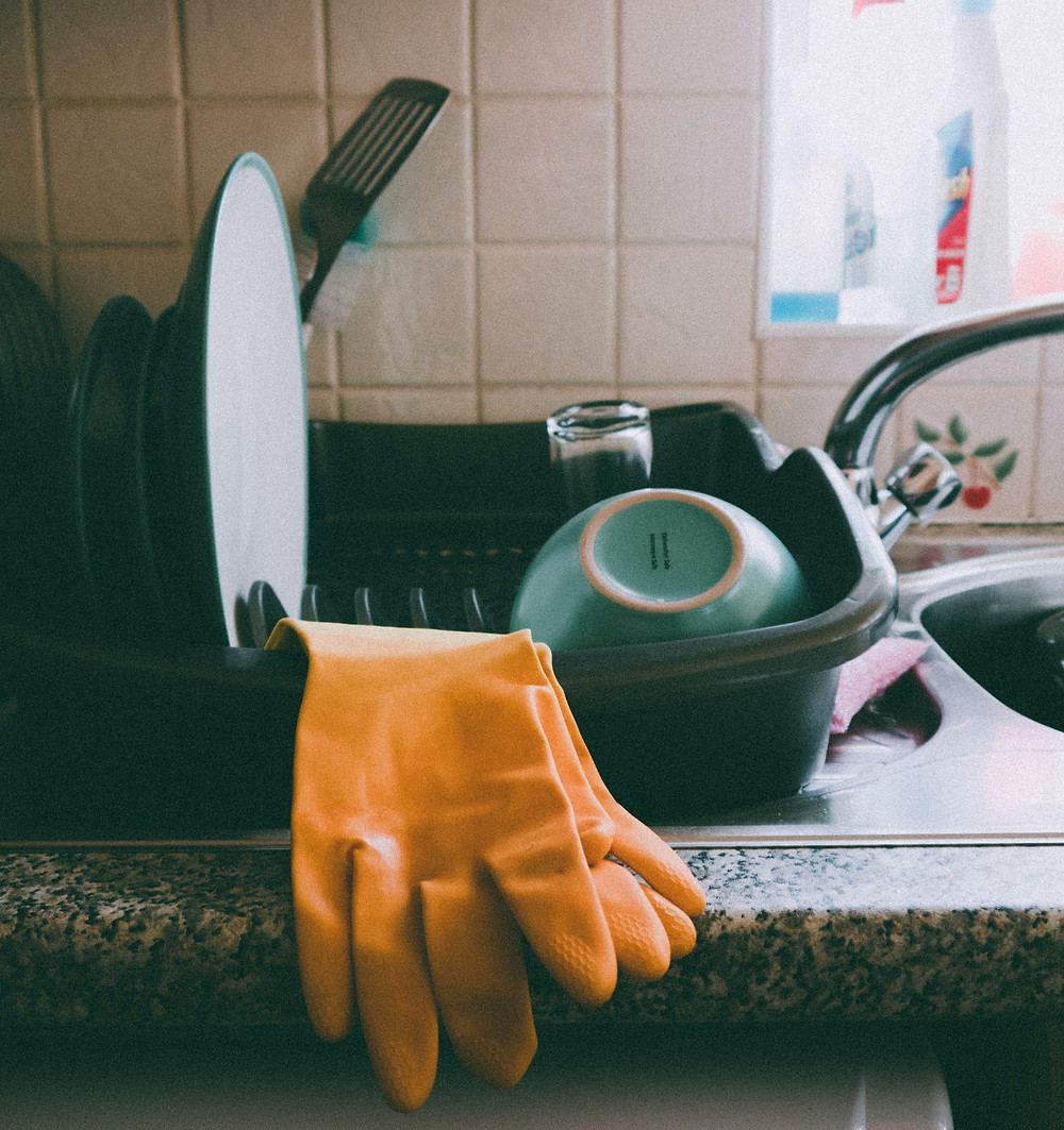 Clean Dishes in a dish rack with gloves.