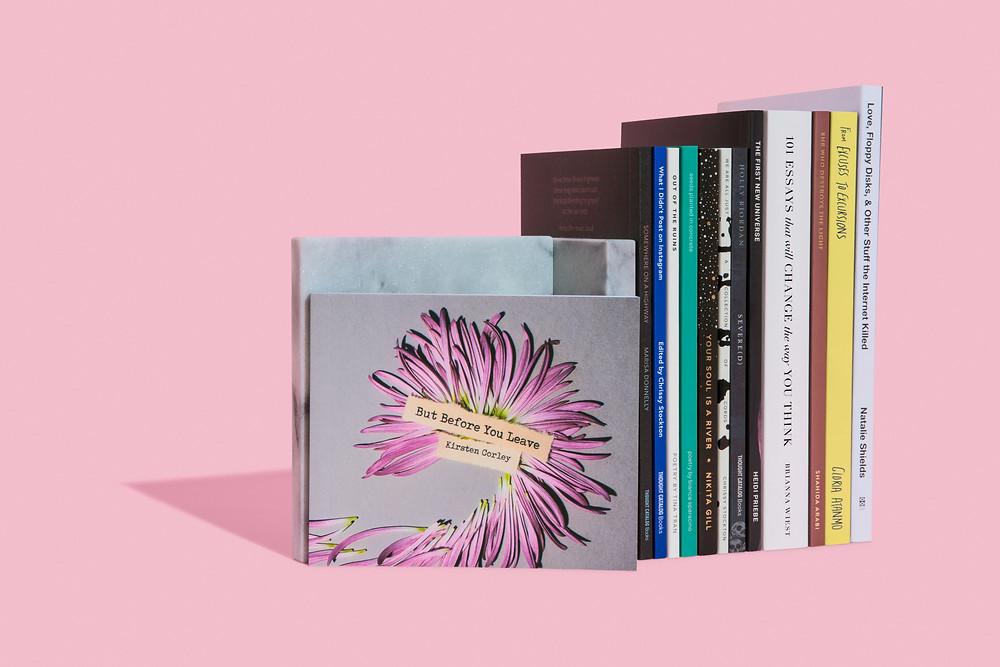 À direita da imagem, cerca de dez livros organizados lado a lado, em pé, apenas com as lombadas aparecendo. Escorado neles, está um quadro com um detalhe em rosa sobre um fundo cinza