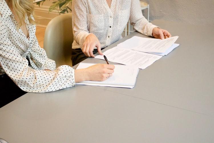 Duas mulheres sentadas a uma mesa de trabalho, lado a lado, em ambiente corporativo, em frente a alguns documentos. Uma delas manuseia os papeis e a outra faz marcações com uma caneta