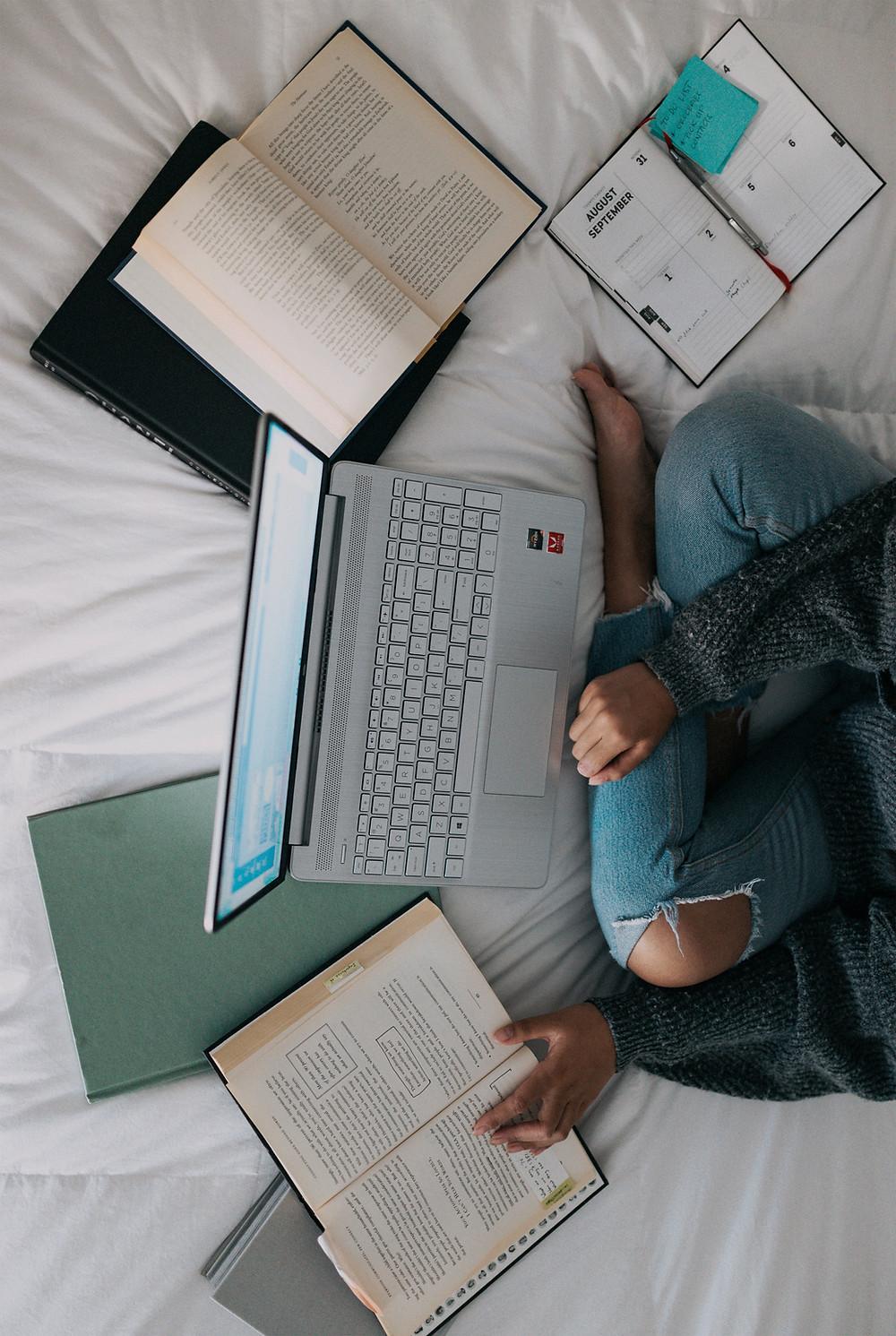 Pessoa sentada sobre a cama, de joelhos dobrados, em frente a um notebook ligado. Do seu lado esquerdo, um livro no qual ela está apoiando a mão. Abaixo do computador, outro livro fechado. Do lado direito, um livro fechado e, sobre ele, outro livro aberto. Ao lado, uma agenda aberta, com um post-it na página direita.