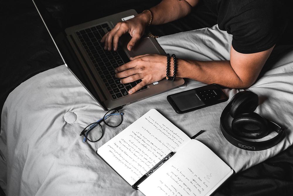 Um homem digitando em um computador, apoiado sobre os cotovelos, em cima da cama. Ao lado do notebook, estão óculos, celular, fones de ouvido, um caderno preenchido com anotações e caneta.