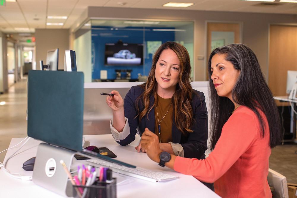 Duas mulheres sentadas em frente a um computador, em uma mesa de trabalho, em ambiente de escritório. Uma delas aponta para a tela com uma caneta, enquanto a outra acompanha o que está sendo apresentado. Sobre a mesa, além do computador, canetas coloridas, teclado e mouse.