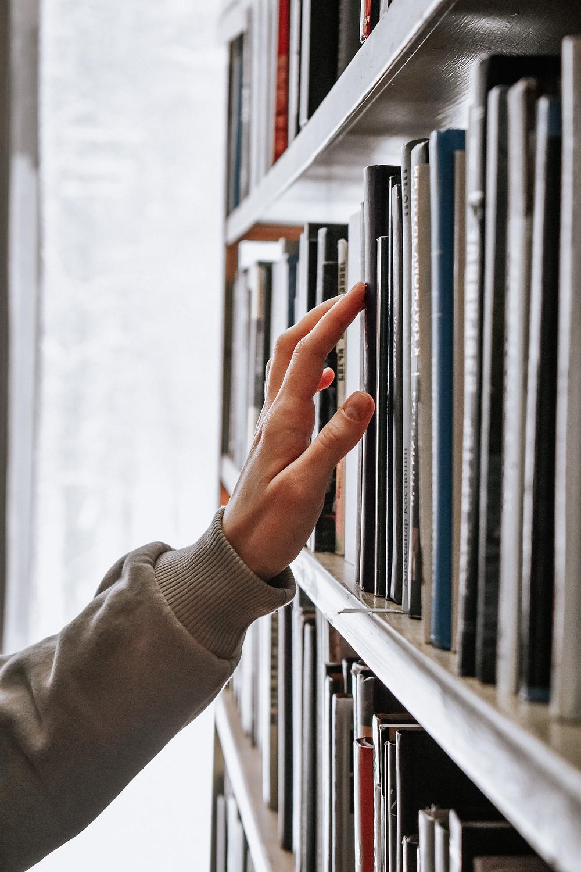 Em frente a uma estante cheia de livros, a imagem mostra a mão de uma pessoa percorrendo as lombadas, conferindo as publicações.