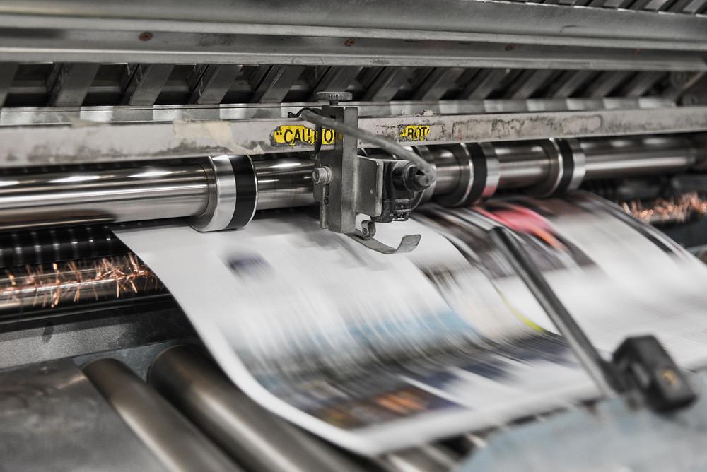 Máquina impressora industrial, estilo rotativa, imprimindo uma página de publicação colorida. Na imagem, vê-se apenas um dos cilindros da máquina.