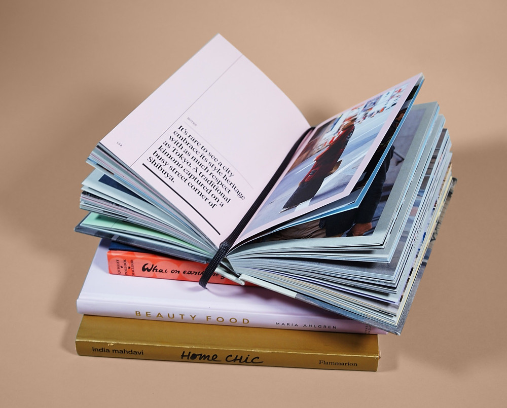 Três livros fechados organizados em uma pilha e, sobre eles, um livro aberto, mostrando uma página com um trecho de texto e a outra com uma fotografia.
