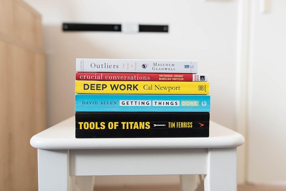 Sobre uma mesa lateral branca, cinco livros empilhados, com títulos em inglês a respeito de temáticas de negócios e metodologias. As capas e lombadas dos livros são coloridas (preto, azul, amarelo, vermelho e branco).
