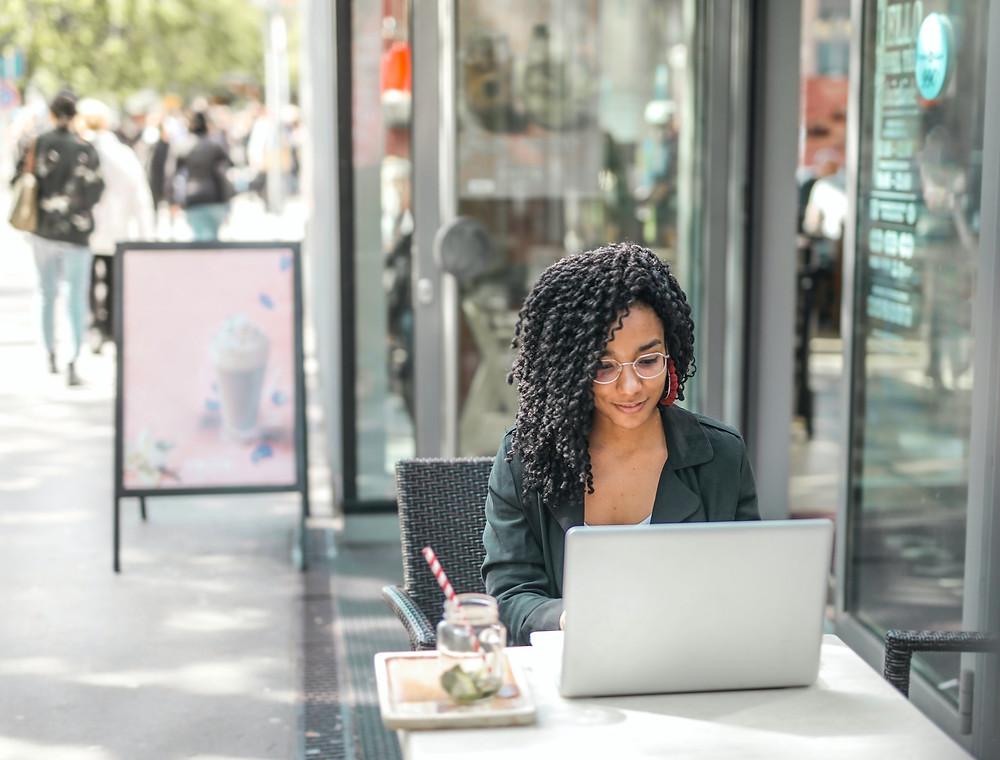 Mulher em frente a um notebook, olhando para a tela, concentrada. Ela está sentada a uma mesa na calçada, em frente a um restaurante ou cafeteria, em um dia ensolarado. Sobre a mesa, um copo de uma bebida refrescante.