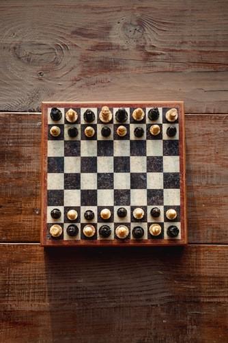 Tabuleiro de xadrez sobre mesa de madeira. As peças pretas e brancas estão misturadas e intercaladas, nas duas fileiras de cima e nas duas fileiras de baixo.
