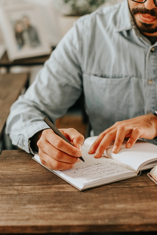 Um homem, sentado a uma mesa de madeira, faz anotações em um caderno. Aparece apenas parte de seu rosto, com barba e óculos. Ao fundo, um porta-retratos e um vaso de flores.