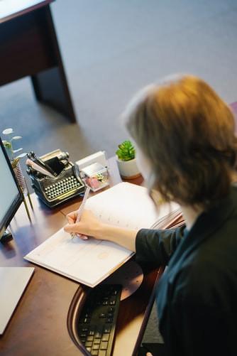Mulher sentada em frente a uma escrivaninha de trabalho, fazendo anotações em uma agenda. À sua frente, uma tela de computador, uma miniatura de máquina de escrever, um porta-papeis de acrílico e um pequeno vaso de planta ornamental