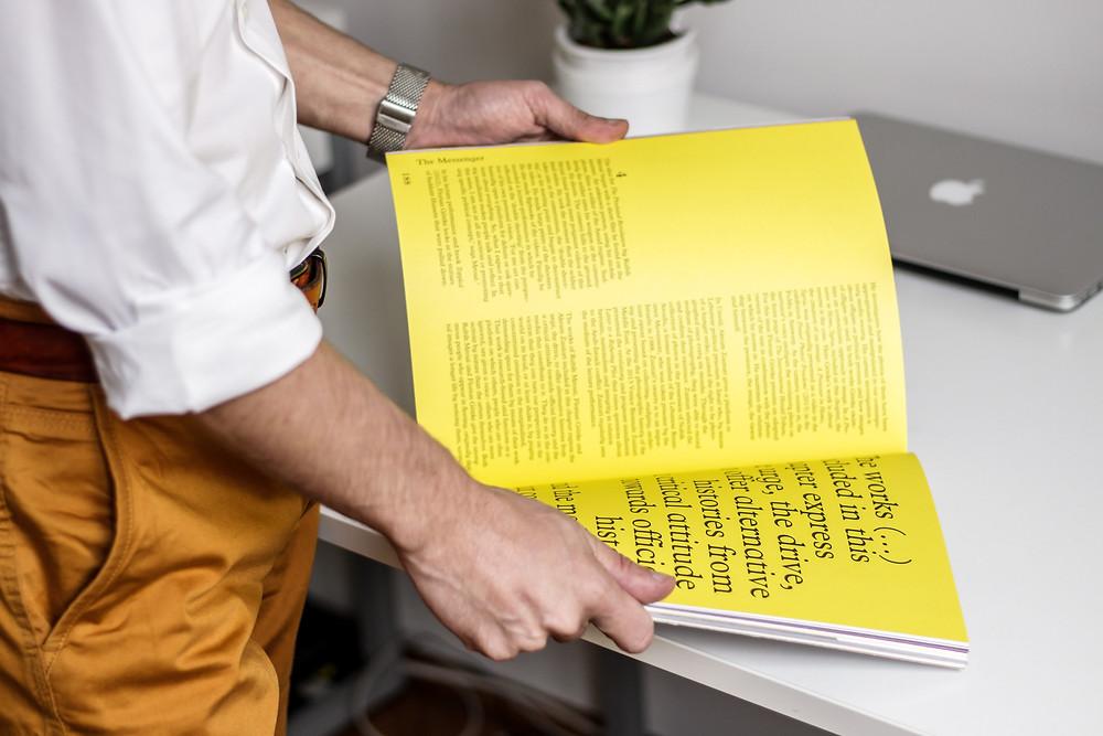 Homem em pé, com apenas parte do corpo enquadrada na imagem, folheando revista que está sobre a mesa. As páginas da revista são amarelas e o texto é distribuído em blocos, com letras pretas em diferentes tamanhos.