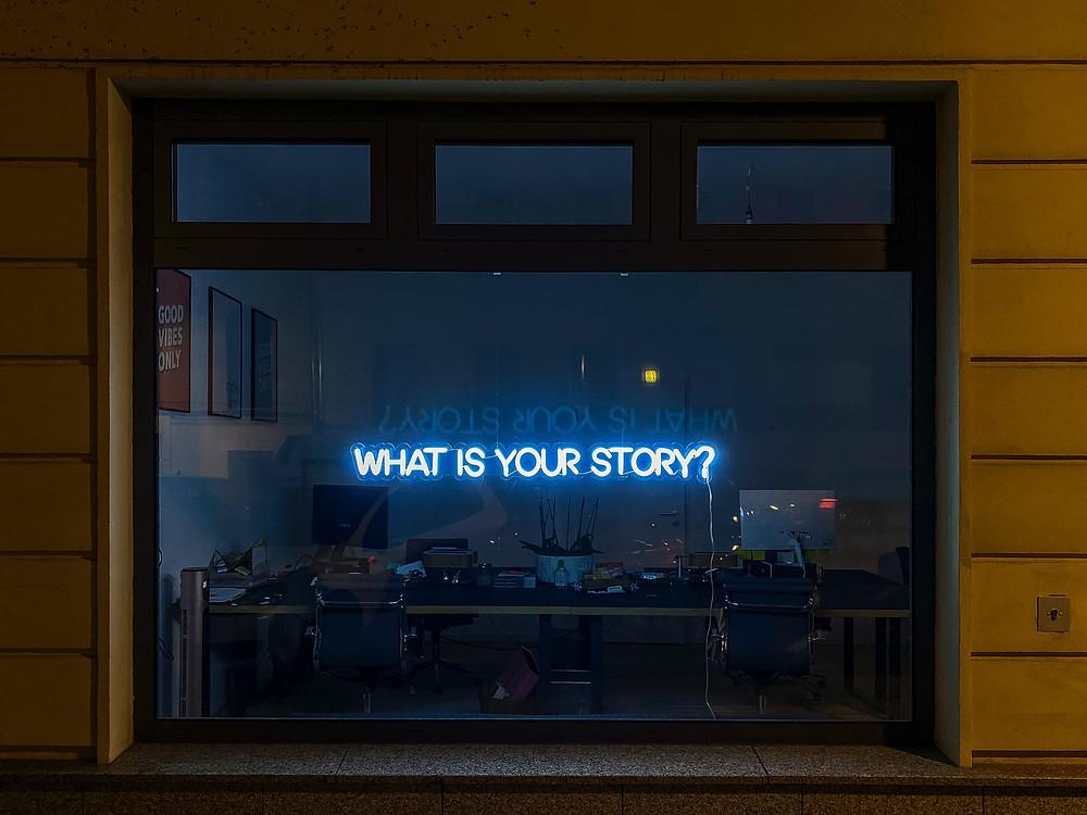 Letreiro luminoso, visto através de uma janela de vidro, no qual está escrito em inglês, em azul e em letras maiúsculas, a pergunta Qual é a sua história?