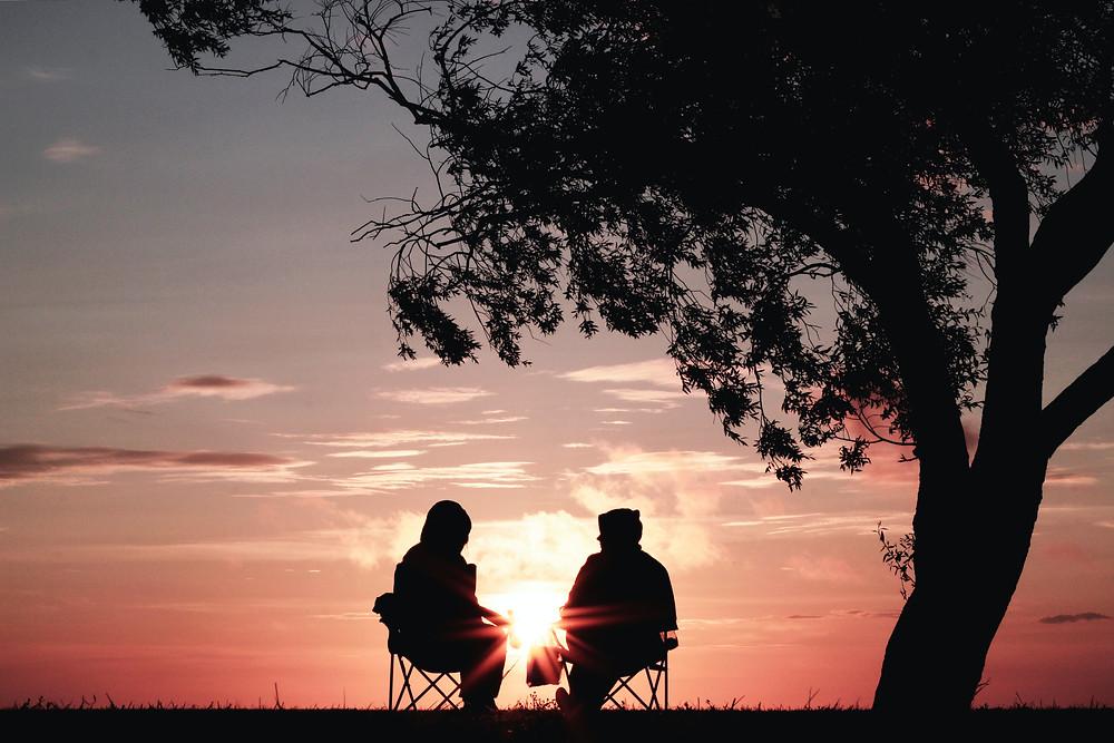 Em um entardecer, à sombra de uma árvore, localizada à direita da foto, duas pessoas estão sentadas conversando. Aparece somente a silhueta delas, demarcada pela luz do sol.