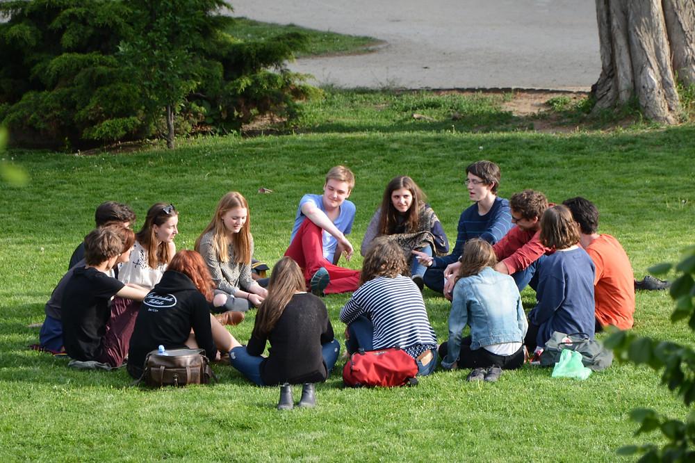 Grupo de 15 jovens, homens e mulheres, com roupas informais, sentados em círculo em um gramado, à luz do dia.