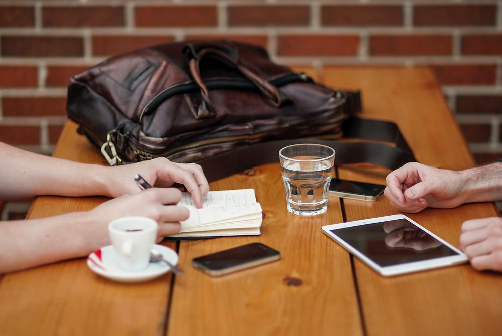 Duas pessoas sentadas frente à frente, a uma mesa de madeira, em um contexto de entrevista ou conversa. Aparecem somente as suas mãos. Uma das pessoas faz anotações em um pequeno bloco de notas. Sobre a mesa, estão também uma pasta, dois celulares, um tablet, um copo com água e uma xícara de café.