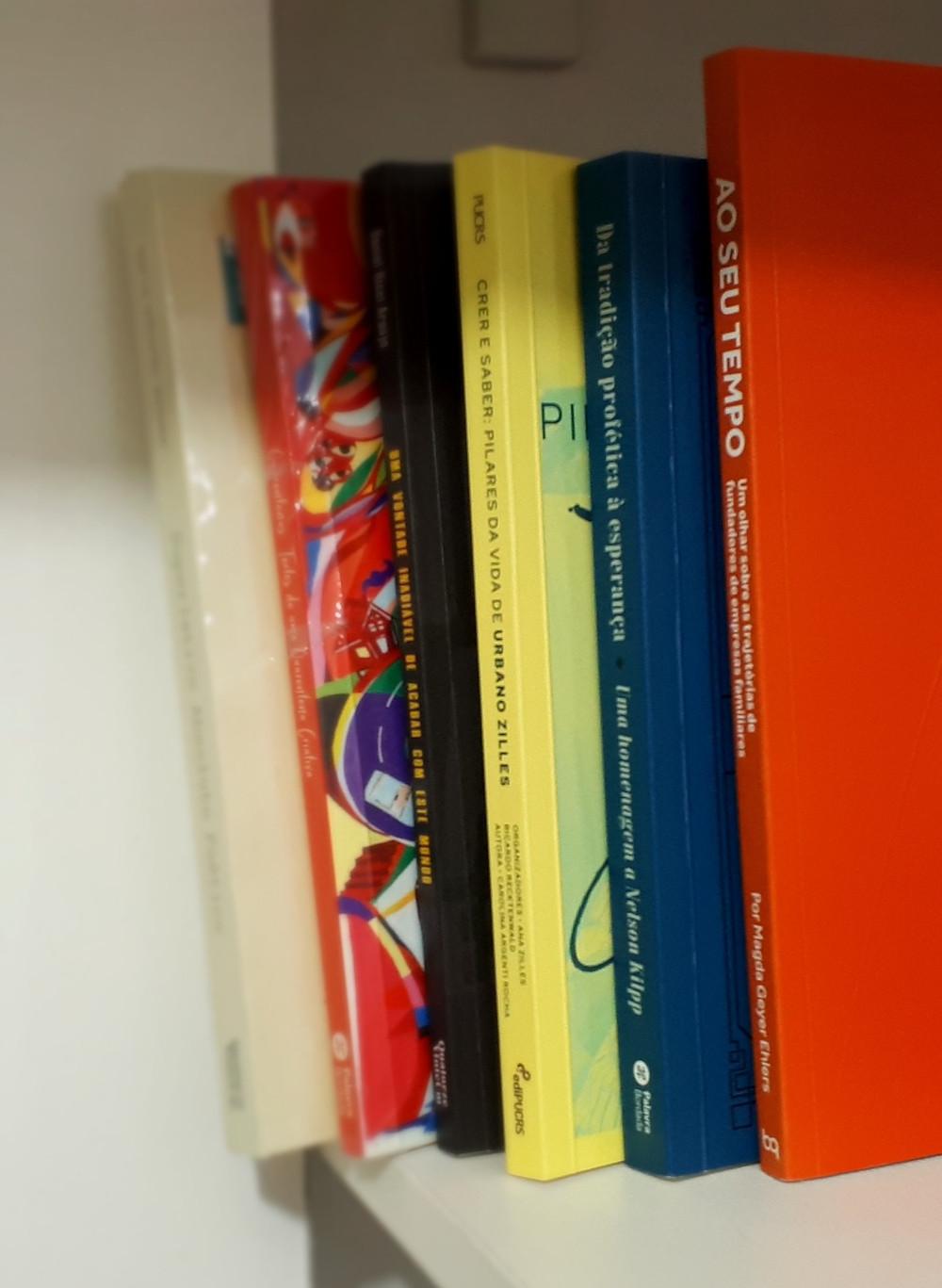 Seis livros dispostos em uma prateleira, em pé, no qual aparece somente a lombada e parte da capa de cada um. São de cores variadas, da esquerda para direita: bege, colorido com fundo vermelho, preto, amarelo, azul e laranja.