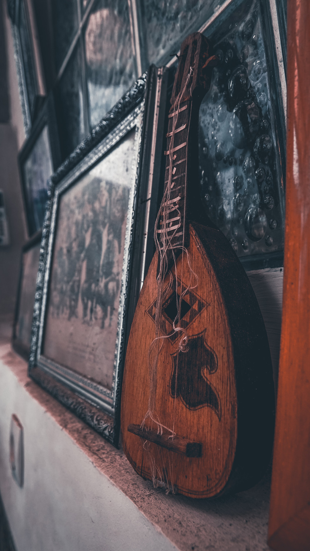 Alaúde com as cordas soltas, escorado à parede, ao lado de quadros com fotos antigas.