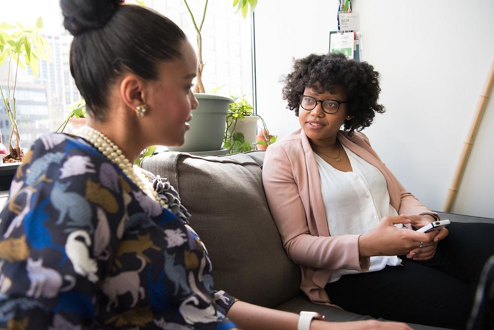 Duas mulheres sentadas em um sofá, lado a lado, olhando-se de frente e conversando, em um ambiente casual, com luz natural e plantas.